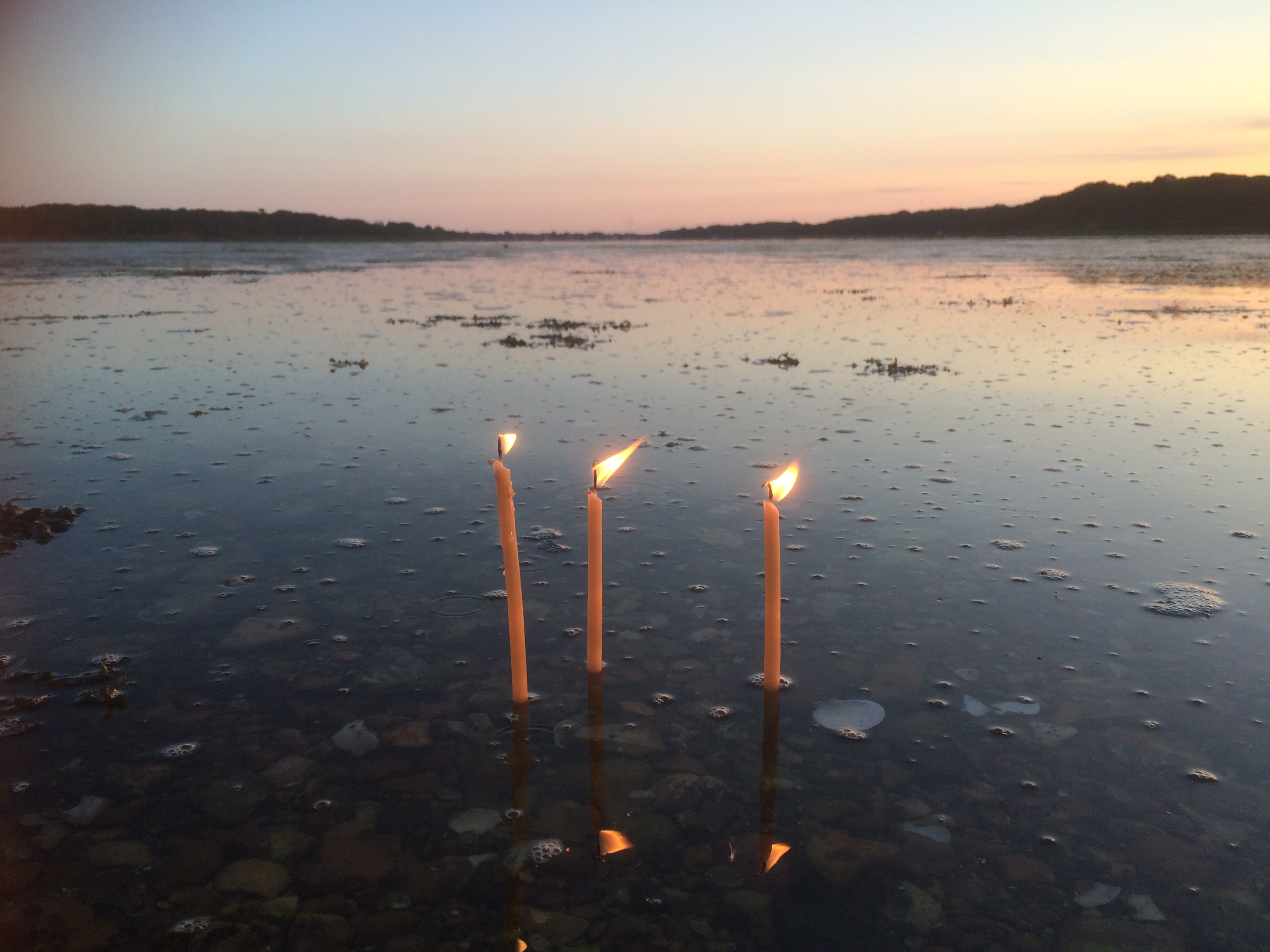 Prayer candles at Sunset on rising tide